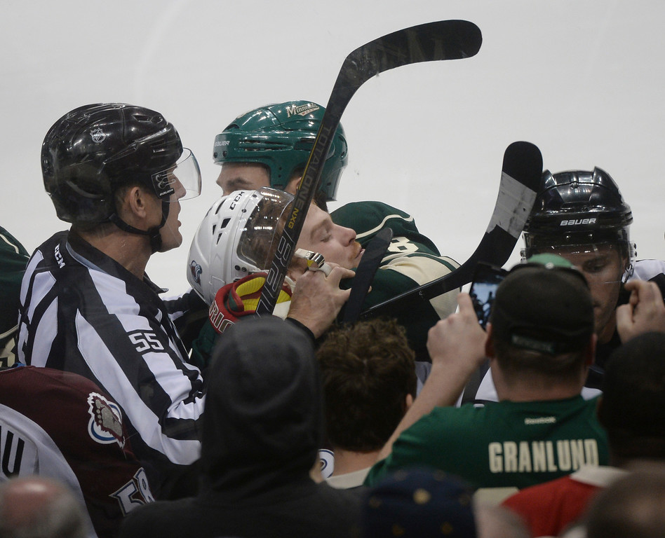 . Linesman Shane Heyer (55) dragged Colorado center Brad Malone out of a scrum in the first period. The Minnesota Wild defeated the Colorado Avalanche 1-0 in overtime at the Xcel Energy Center in St. Paul Monday night, April 21, 2014. (Photo by Karl Gehring/The Denver Post)