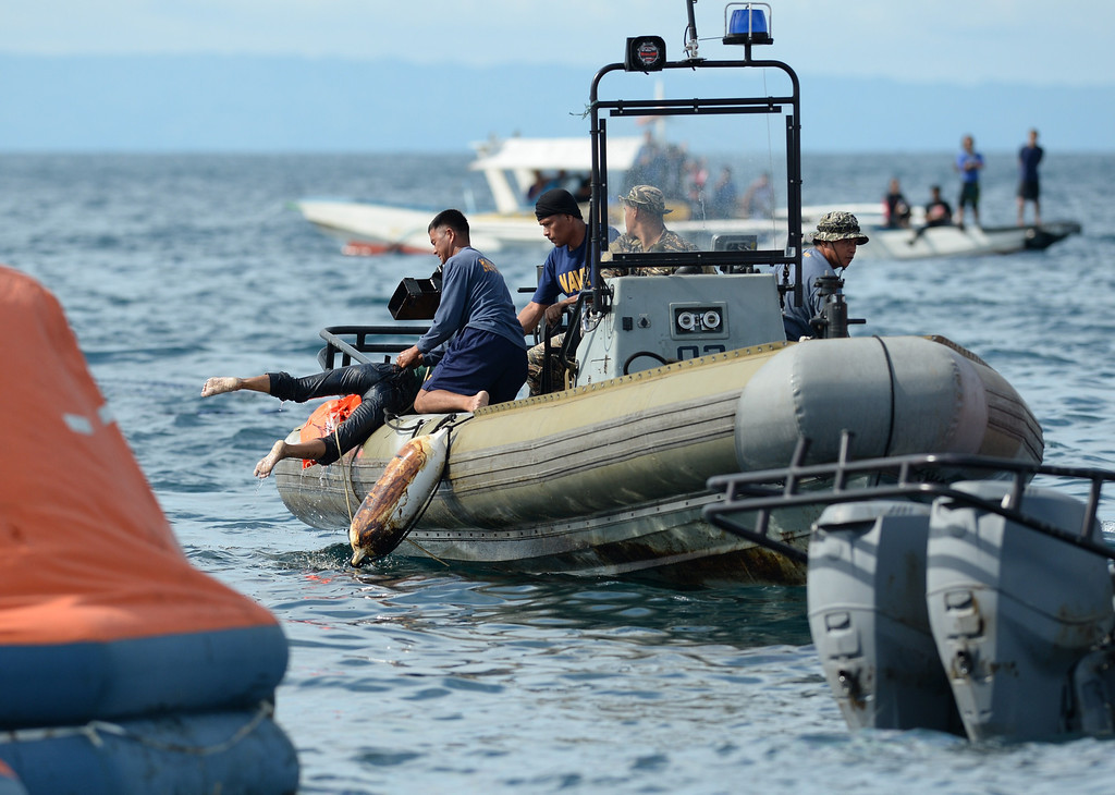 . Philippine Navy personnel retrieve a dead body from the sea believed to be one of the passengers from the sunken ferry St. Thomas Aquinas on August 17, 2013 after it collided with a cargo ship the night before off the town of Talisay near the Philippines\' second largest city of Cebu. Philippine rescuers searched on August 17 for more than 200 people missing after the ferry collided with the cargo ship in thick darkness and sank almost instantly, with 26 already confirmed dead. TED ALJIBE/AFP/Getty Images
