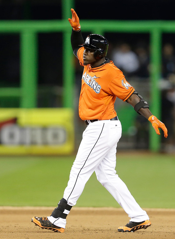 . Miami Marlins\' Marcell Ozuna celebrates after hitting a double during the fifth inning of an opening day baseball game against the Colorado Rockies, Monday, March 31, 2014, in Miami. (AP Photo/Lynne Sladky)