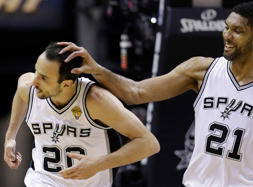 . After dunking against the Miami Heat, San Antonio Spurs guard Manu Ginobili (20) is congratulated by forward Tim Duncan (21) during the first half in Game 5 of the NBA basketball finals on Sunday, June 15, 2014, in San Antonio. (AP Photo/David J. Phillip)