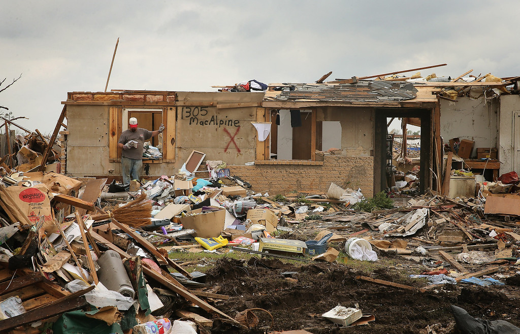 . A worker cleans out a tornado-damaged home May 26, 2013 in Moore, Oklahoma. U.S. President Barack Obama toured the area today.  (Photo by Scott Olson/Getty Images)