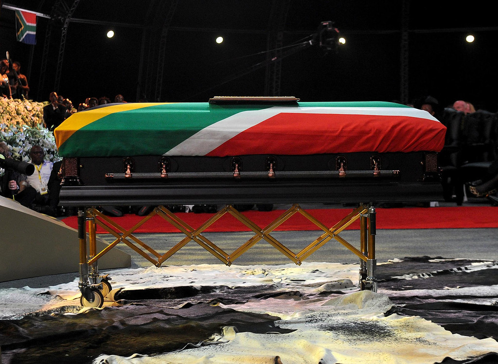 . The casket of Nelson Mandela stands on cow skins during his funeral service in Qunu, South Africa Sunday, Dec. 15, 2013.  (AP Photo/Elmond Jiyane, GCIS)
