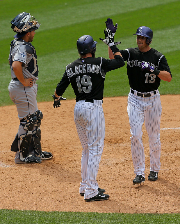 . DENVER, CO - JULY 9:  Drew Stubbs #13 of the Colorado Rockies celebrates his two run home run with Charlie Blackmon #19 as catcher Yasmani Grandal #8 of the San Diego Padres looks on during the eighth inning at Coors Field on July 9, 2014 in Denver, Colorado. (Photo by Justin Edmonds/Getty Images)