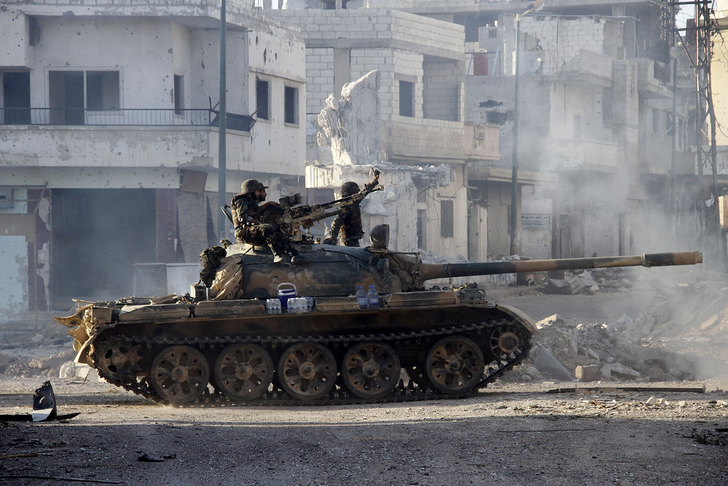 . Syrian army troops drive through the ravaged streets of Qusayr in the central Homs province on June 5, 2013, after government forces seized total control of the former rebel-stronghold. The United States condemned the assault by Syrian troops on Qusayr, claiming the regime had had to depend on the Lebanese militant group Hezbollah to win the battle, causing tremendous suffering during a blistering 17-day assault which ended in a major battlefield success for regime forces in a war that has killed at least 94,000 people.   AFP PHOTO / STR-/AFP/Getty Images