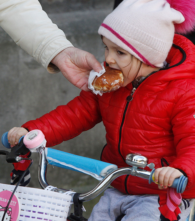 . A little girl indulges in Poland\'s tradition of eating jam-filled doughnuts, or Paczki after having stood in line for some three hours to get the cakes traditionally eaten on the last Thursday of carnival, the Fat Thursday in Warsaw, Poland, Feb. 27, 2014. Long lines in front of sweet shops are a traditional sight in Poland on this Thursday. (AP Photo/Czarek Sokolowski)