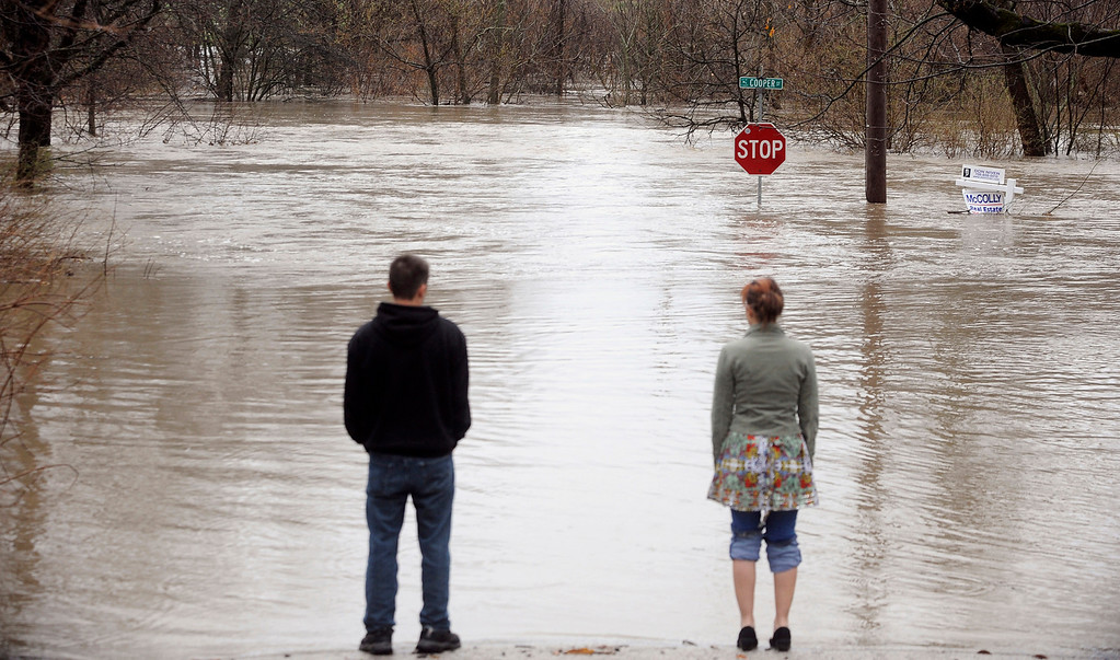 . Joe Stoffey, left, and his partner, Chrissy Wild, look at the flooded Hickory Creek Thursday April 18,  2013, as it passes near the home they were going to buy in New Lenox, Ill., after torrential rains swept through the area. (AP Photo/SouthtownStar, Matt Marton)