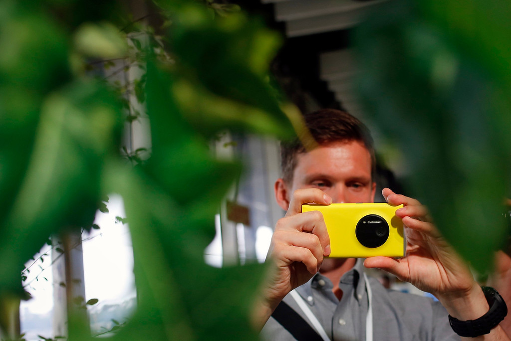 . A man takes pictures with Nokia\'s new smartphone, the Lumia 1020 with a 41-megapixel camera, after its unveiling in New York July 11, 2013.    REUTERS/Shannon Stapleton