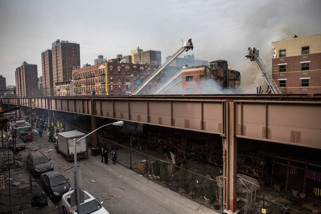 . Seen from behind the Metro North elevated train line, firefighters from the Fire Department of New York (FDNY) respond to a 5-alarm fire and building collapse at 1646 Park Ave in the Harlem neighborhood of Manhattan March 12, 2014 in New York City.  (Photo by Andrew Burton/Getty Images)