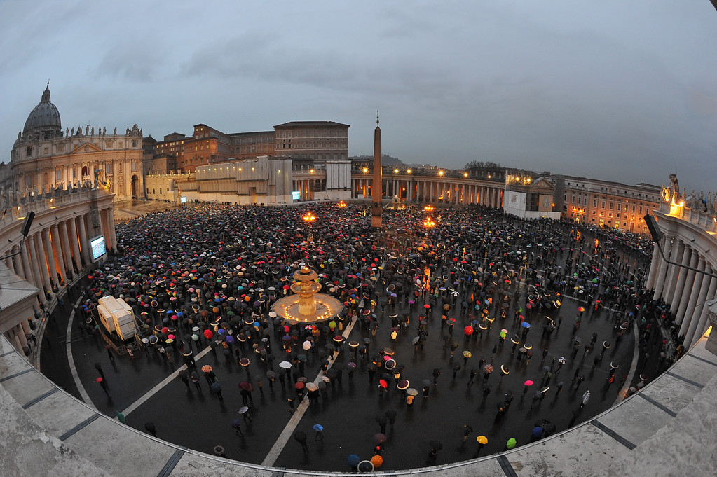 . Faithfuls wait under their umbrellas at St Peter\'s square for the smoke announcing the result on the second day of the papal election conclave on March 13, 2013 at the Vatican.  AFP PHOTO / TIZIANA  FABI/AFP/Getty Images