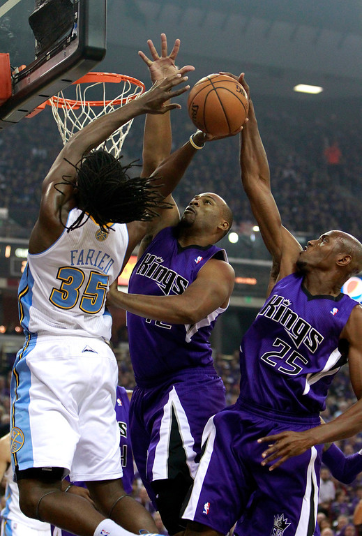 . Denver Nuggets forward Kenneth Faried, left, is fouled by Sacramento Kings forward Travis Outlaw, right, during the first quarter of an NBA basketball game in Sacramento, Calif., Wednesday, Oct. 30, 2013.  In the center is Kings forward Chuck Hayes. (AP Photo/Rich Pedroncelli)