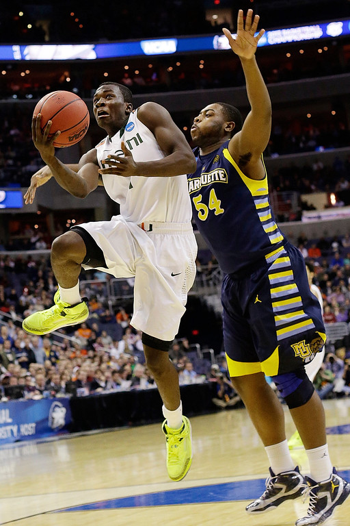 . Miami guard Durand Scott (1) shoots under pressure from Marquette forward Davante Gardner (54) during the second half of an East Regional semifinal in the NCAA college basketball tournament, Thursday, March 28, 2013, in Washington. (AP Photo/Pablo Martinez Monsivais)