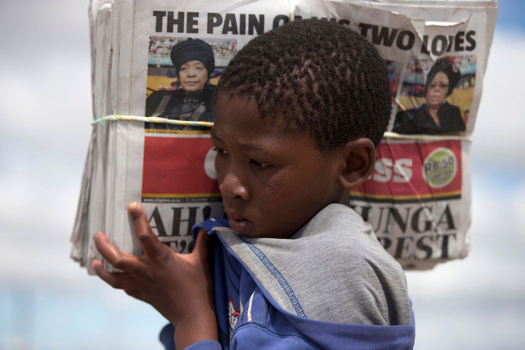 ". A young boy carries a stack of newspapers with a picture of Winnie Madikizela-Mandela, left, Nelson Mandela\'s former wife, and Nelson Mandelaís widow Graca Machel, right,  with a headline reading ""The Pain Of His Two Loves\"" during the burial of the former South African President and iconic leader in his hometown Qunu, South Africa, Sunday Dec. 15, 2013. (AP Photo/Peter Dejong)"