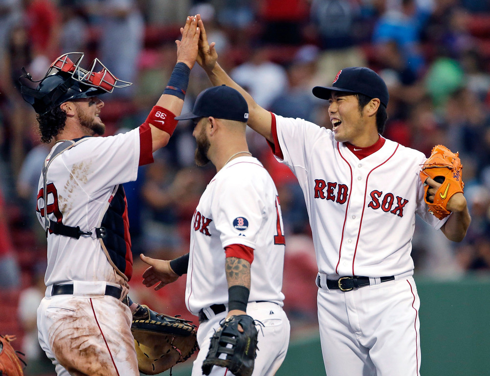 . Boston Red Sox closer Koji Uehara celebrates with catcher Jarrod Saltalamacchia, left, with Mike Napoli at center, after the Red Sox defeated the Colorado Rockies 5-3 in an interleague baseball game at Fenway Park in Boston, Wednesday, June 26, 2013. (AP Photo/Elise Amendola)