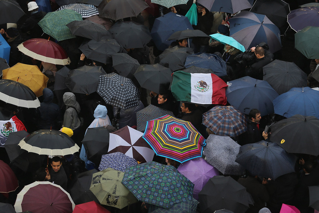 . People shelter from the rain under umbrellas as they gather in St Peter\'s Square for news on the election of a new Pope on March 13, 2013 in Vatican City, Vatican.  (Photo by Joe Raedle/Getty Images)
