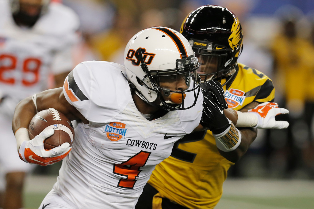 . Oklahoma State quarterback J.W. Walsh (4) gets past Missouri defensive back Duron Singleton (2) during the second half of the Cotton Bowl NCAA college football game on Friday, Jan. 3, 2014, in Arlington, Texas. (AP Photo/Brandon Wade)