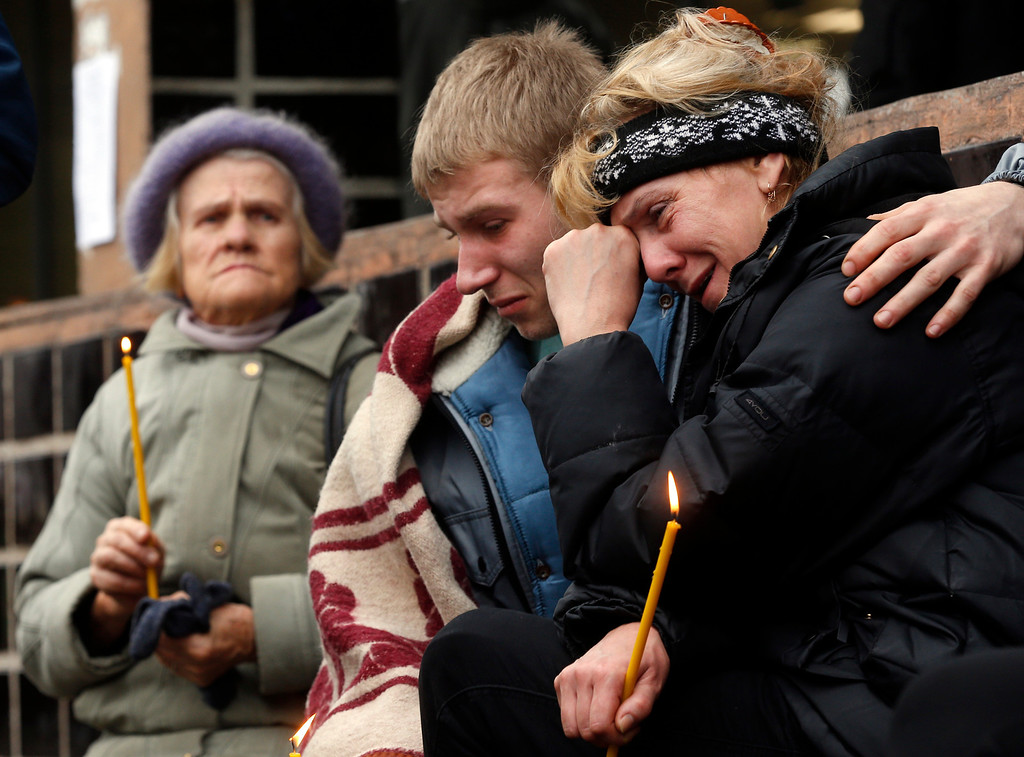 . Passers by react outside the collapsed Maxima supermarket in Riga, Latvia, Saturday, Nov. 23, 2013.   (AP Photo/Mindaugas Kulbis)