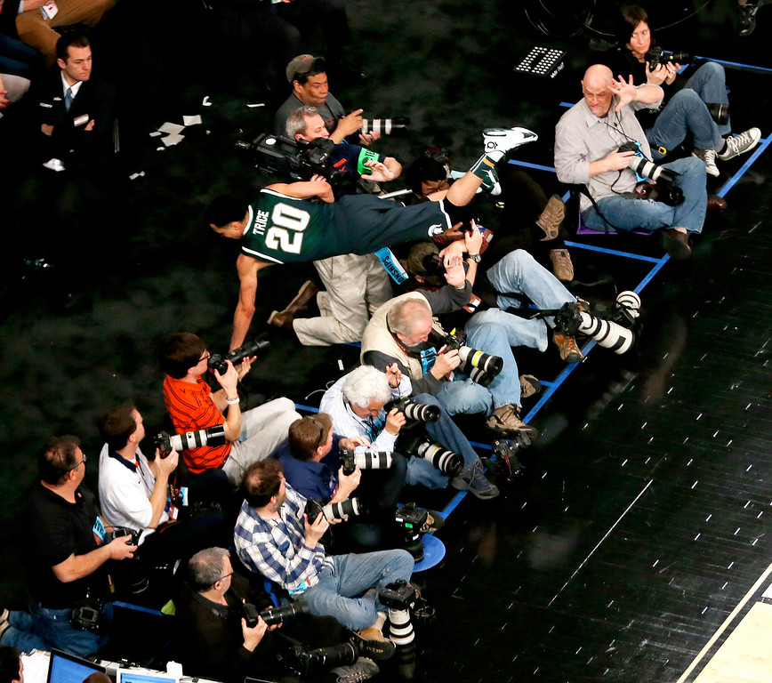 . Michigan State guard Travis Trice (20) dives over photographers after trying to keep a ball in bounds during second half in a regional semifinal against Virginia at the NCAA men\'s college basketball tournament, Friday, March 28, 2014, in New York. (AP Photo/Julio Cortez)