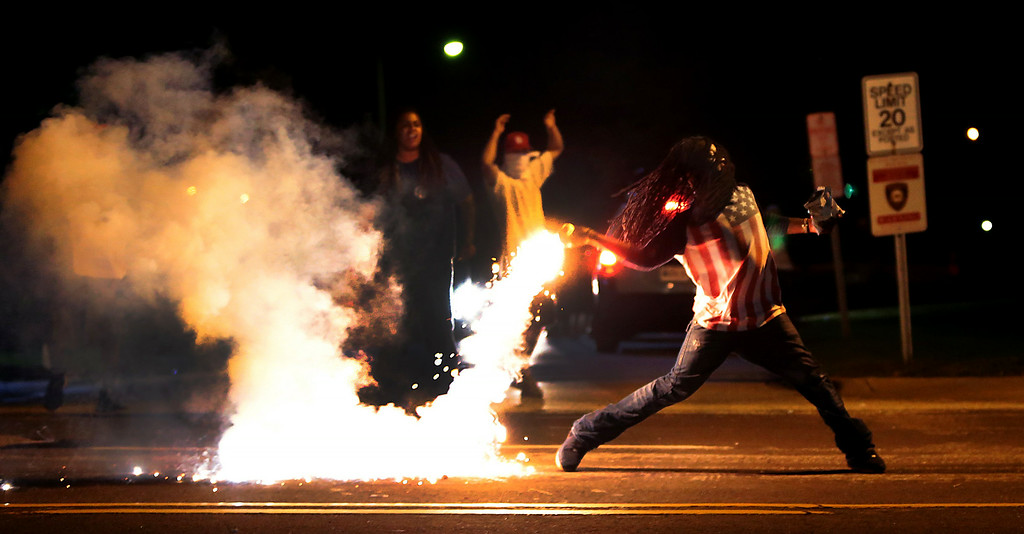 . A demonstrator throws back a tear gas container after tactical officers try to break up a group of bystanders Wednesday, Aug. 13, 2014 in West Florissant, Mo. Ferguson has been the site of nightly protests and unrest since 18-year-old Michael Brown was killed during a confrontation with an officer on Saturday. (AP Photo/St. Louis Post-Dispatch, Robert Cohen)