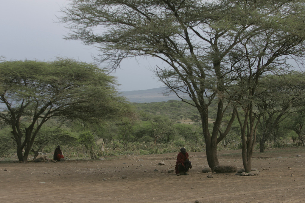. Masai tribesmen squat in the shade near their village on the edge of the Ngorongoro Crater in Tanzania, Africa.