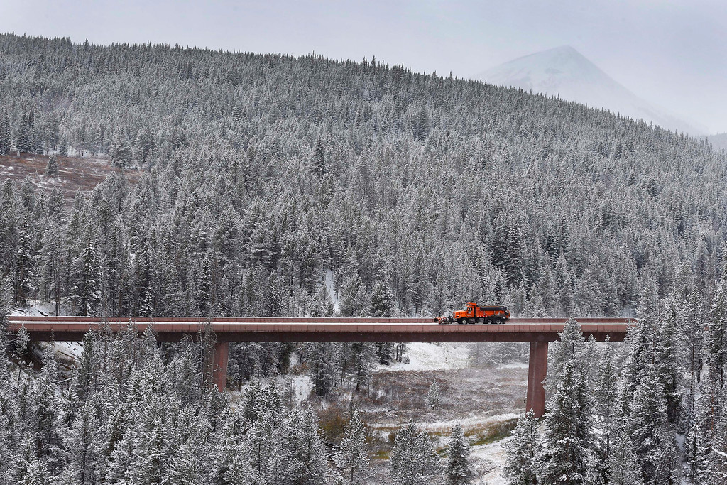 . A truck plows an elevated section of I-70 after overnight snow fell near Copper Mountain, Colo., Friday Oct. 4, 2013. Powerful storms moved into the Midwest on Friday due to a cold weather system gaining strength as it traveled east from Colorado and Wyoming. (AP Photo/Brennan Linsley)