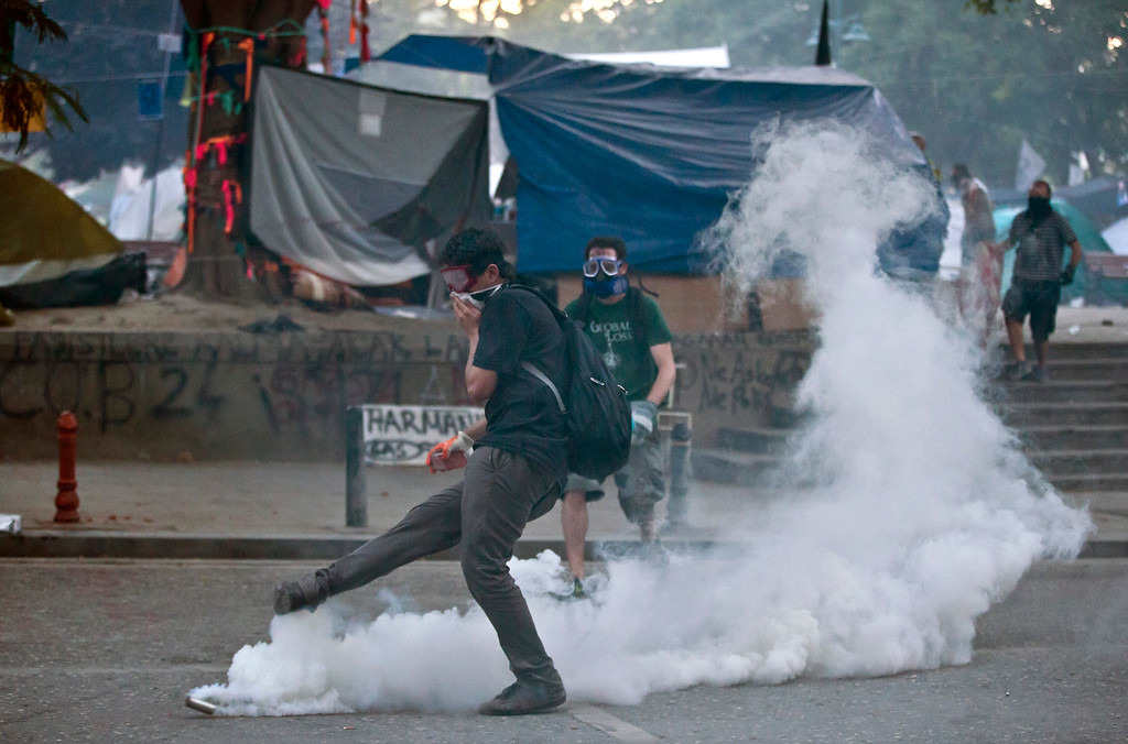 . A protester kicks a canister after riot police flooded the Gazi Park with tear gas during clashes at the Taksim Square in Istanbul Tuesday, June 11, 2013.  (AP Photo/Vadim Ghirda)