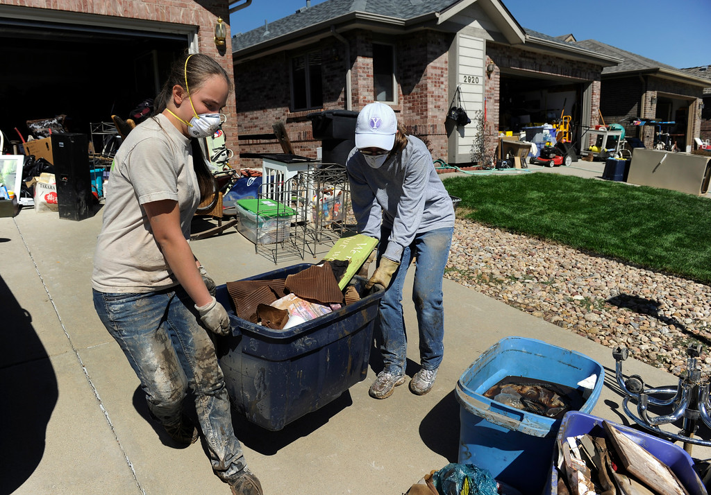 . LONGMONT, CO - Sept. 20: Members of Grace Church in Longmont, Lizzy Greenidge, left, 13, and Jill Stolte, 21, remove sludge-covered items from the basement of Maryellen Boop who says she lost just about everything from that room. Residents along Wade Rd. just south of the Twin Peaks Golf Course continue the cleanup after floods last week devastated the neighborhood. (Photo By Kathryn Scott Osler/The Denver Post)