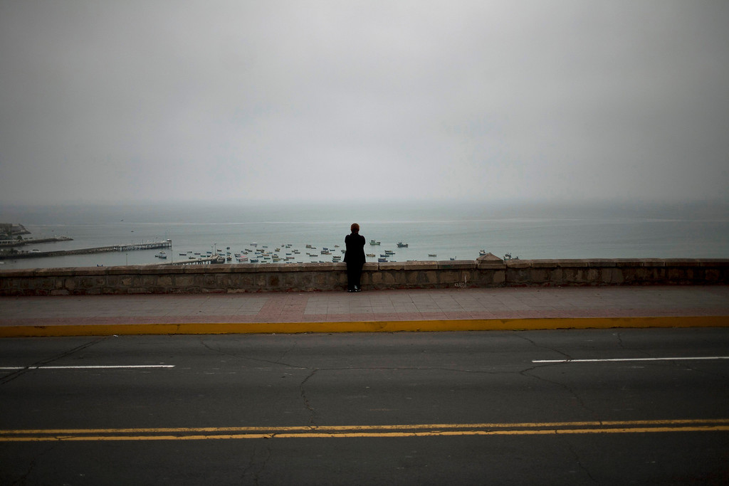 ". In this July 3, 2013 photo, a woman watch at the Pacific Ocean from a waterfront promenade in the Chorrillos neighborhood of Lima, Peru. For roughly four months a year, the sun abandons Peru\'s seaside desert capital, suffocating it under a ponderous gray cloudbank and fog that coats the city with nighttime drizzles. The cold Humboldt current that runs north from Antarctica along the coast is the culprit, colliding with the warmer tropical atmosphere to create the blinding mists called ""garua\"" in coastal Chile and Peru. (AP Photo/Rodrigo Abd)"