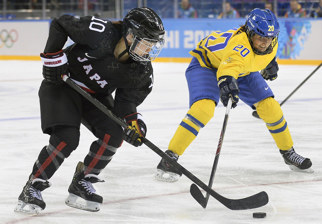 . Japan\'s Haruna Yoneyama (L) vies with Sweden\'s Fanny Rask during the Women\'s Ice Hockey Group B match Sweden vs Japan at the Shayba Arena during the Sochi Winter Olympics on February 9, 2014.     ALEXANDER NEMENOV/AFP/Getty Images