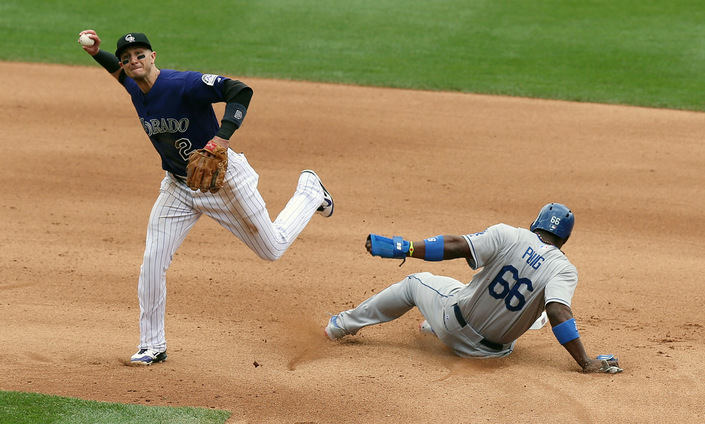 . Colorado Rockies shortstop Troy Tulowitzki, left, throws to first base after forcing out Los Angeles Dodgers\' Yasiel Puig at second base on the front end of a double play hit into by Adrian Gonzalez to end the top of the fourth inning of a baseball game in Denver on Saturday, June 7, 2014. (AP Photo/David Zalubowski)