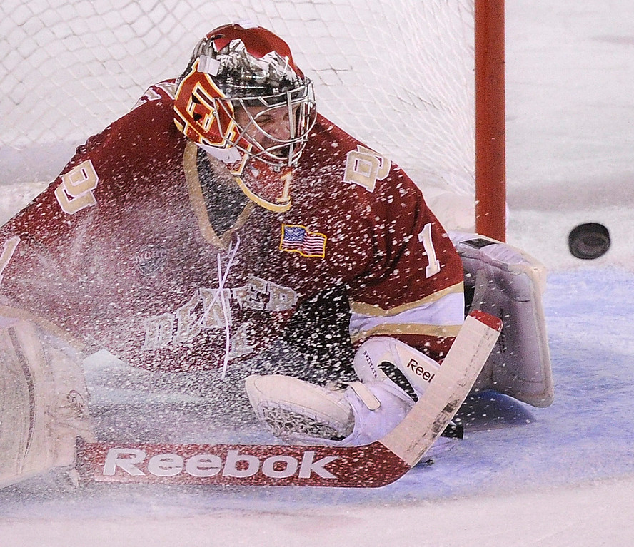 . DENVER, CO. - OCTOBER 25: Denver goalkeeper Sam Brittain was showered with ice as he made a stop in the second period. The University of Denver hockey team hosted Niagara at Magness Arena Friday night, October 25, 2013. Photo By Karl Gehring/The Denver Post