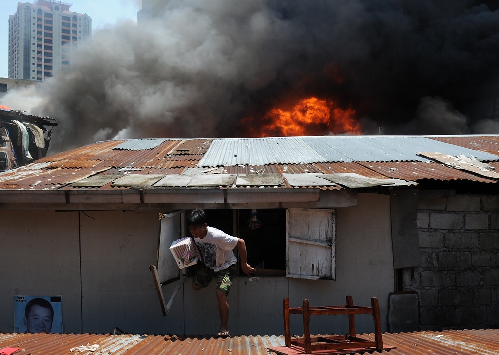 . A resident (C) carrying salvaged belongings escapes out of a window of his burning house as a fire engulfs a shanty town in the financial district of Manila on July 11, 2013, leaving more than 1,000 people homeless according to city officials. There were no immediate reports of casualties from the blaze, which occurred mid-morning amid government plans to relocate thousands of families living in areas vulnerable to floods and typhoons. TED ALJIBE/AFP/Getty Images