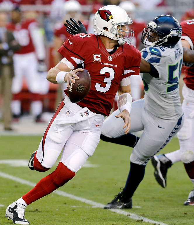 . Arizona Cardinals quarterback Carson Palmer (3) scrambles under pressure from Seattle Seahawks defensive end Cliff Avril (56) during the first half of an NFL football game, Thursday, Oct. 17, 2013, in Glendale, Ariz. (AP Photo/Ross D. Franklin)