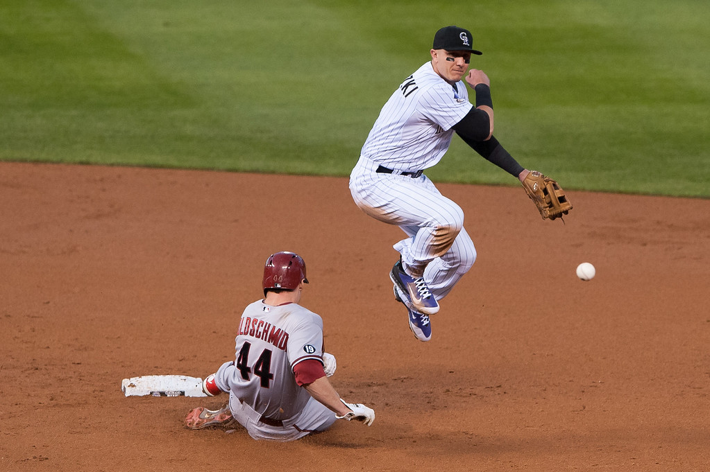 . DENVER, CO - SEPTEMBER 20:  Troy Tulowitzki #2 of the Colorado Rockies turns a third-inning double play past a sliding Paul Goldschmidt #44 of the Arizona Diamondbacks during a game at Coors Field on September 20, 2013 in Denver, Colorado. (Photo by Dustin Bradford/Getty Images)