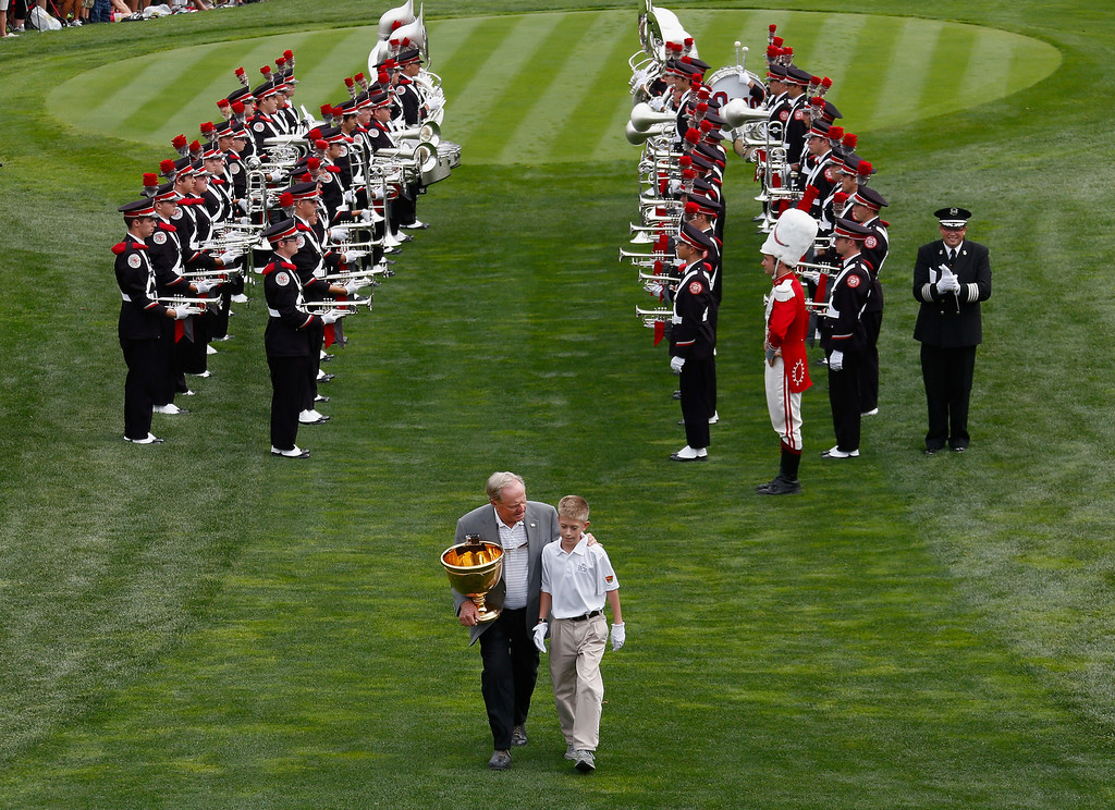 . DUBLIN, OH - OCTOBER 03:  Presidents Cup host Jack Nicklaus walks past the Ohio State University marching band with junior golfer Grant Kresina prior to the start of the Day One Four-Ball Matches at the Muirfield Village Golf Club on October 3, 2013  in United States, Ohio  (Photo by Gregory Shamus/Getty Images)