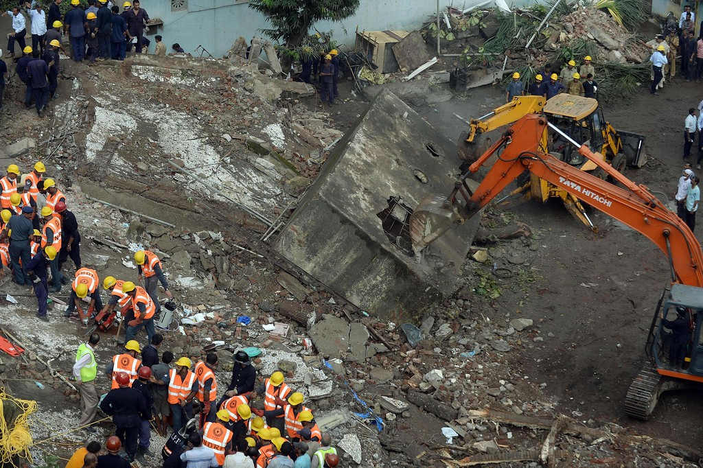 . Firefighters and rescue workers carry a body from the site of a building collapse in Mumbai on September 27, 2013.  A five-story residential block collapsed in Mumbai at daybreak killing at least three people and leaving up to 70 feared trapped inside, in the latest building disaster to hit India\'s financial capital . AFP PHOTO/ PUNIT PARANJPE/AFP/Getty Images