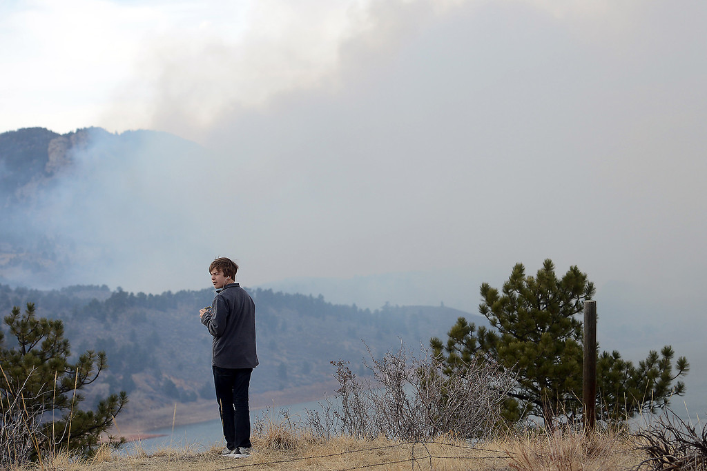 . Windsor resident Zachary Brumley, 13, watches a plume of smoke from the Galena fire while standing on a hillside east of Horsetooth Reservoir on Friday, March 15, 2013. (Steve Stoner/Loveland Reporter-Herald)