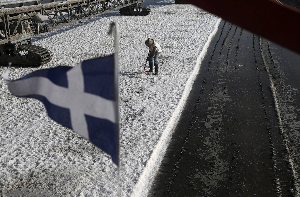 . A Greek flag flies as a worker shovels salt at a production site in Messolongi, western Greece, on Monday Sept. 30, 2013. Salt lakes at Messolongi are used for production by solar evaporation. The facilities are the largest saltworks in Greece, and are located at a protected wetland complex of estuaries and lagoons. (AP Photo/Dimitri Messinis)