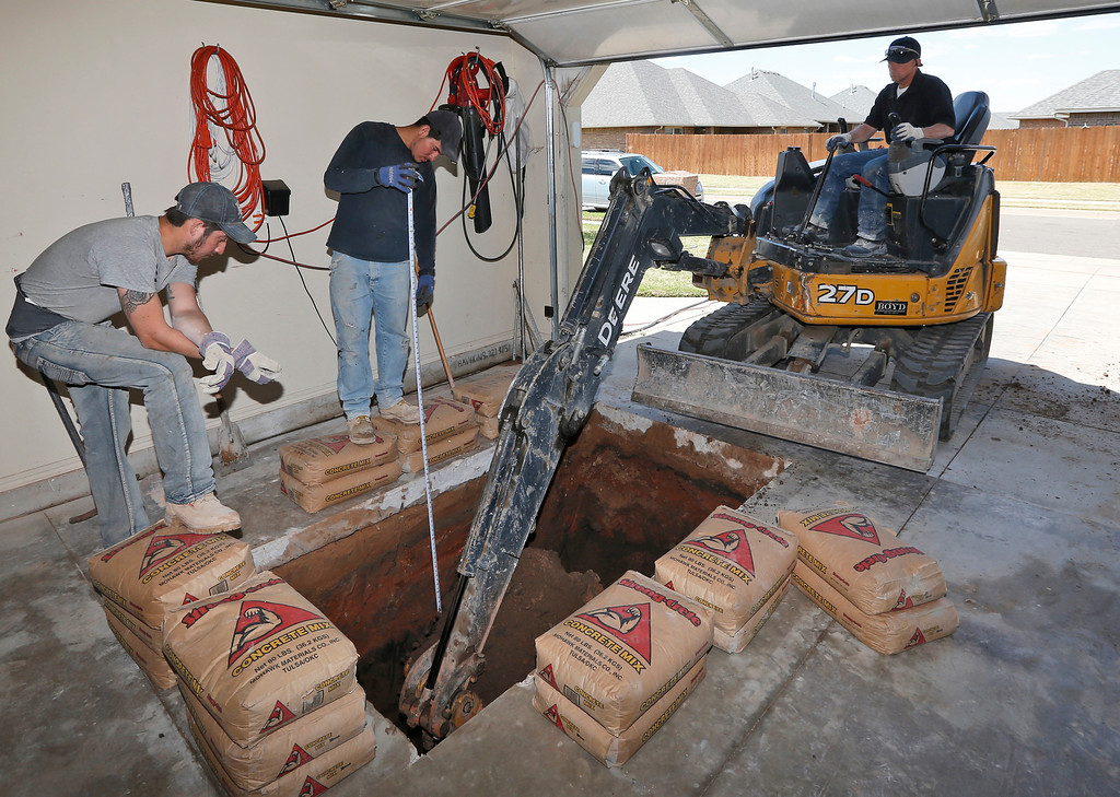 . In this Thursday, May 1, 2014 photo, Thunderground Storm Shelters\' Dustin Wagner, left, and Jacob Ortiz, center, assist as Jim Hohnsbehn digs a hole for a storm shelter in the garage at a residence in Oklahoma City. Last year\'s deadly tornadoes, which killed more than 30 people, scared Oklahomans in a way that previous storms had not, moving them to add tornado shelters or reinforced safe rooms to their homes. In fact, surging demand has overwhelmed companies that build the shelters. (AP Photo/Sue Ogrocki)