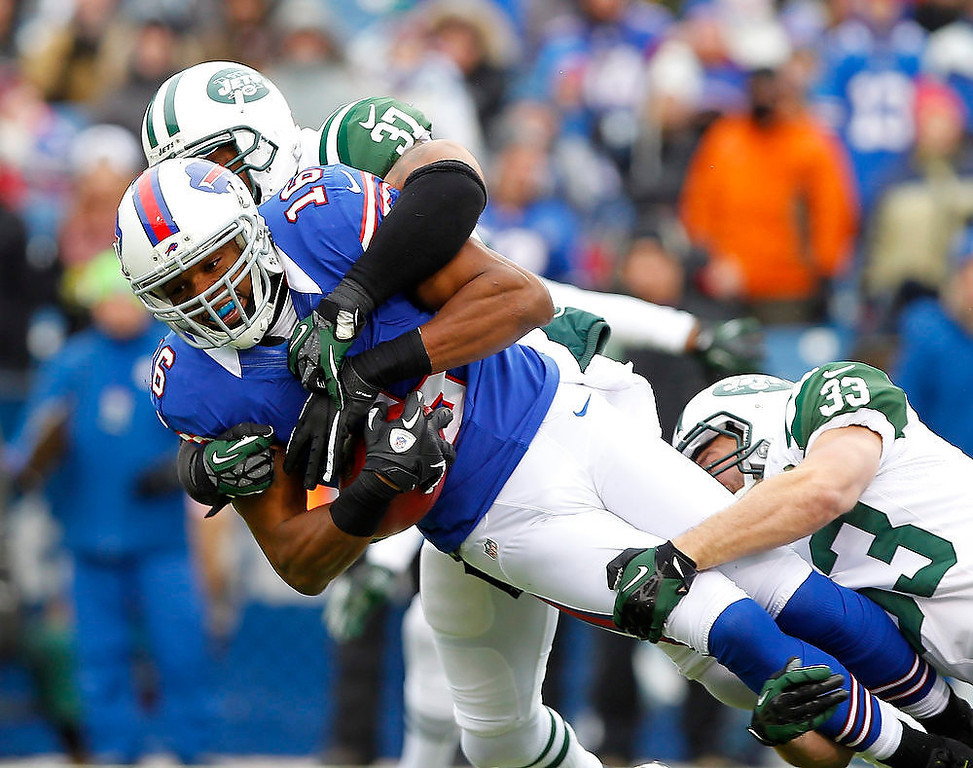 . Buffalo Bills\' Brad Smith (16) is tackled by New York Jets defenders Yeremiah Bell (37) and Eric Smith (33) on a kickoff return during the second half of an NFL football game on Sunday, Dec. 30, 2012, in Orchard Park, N.Y. (AP Photo/Bill Wippert)