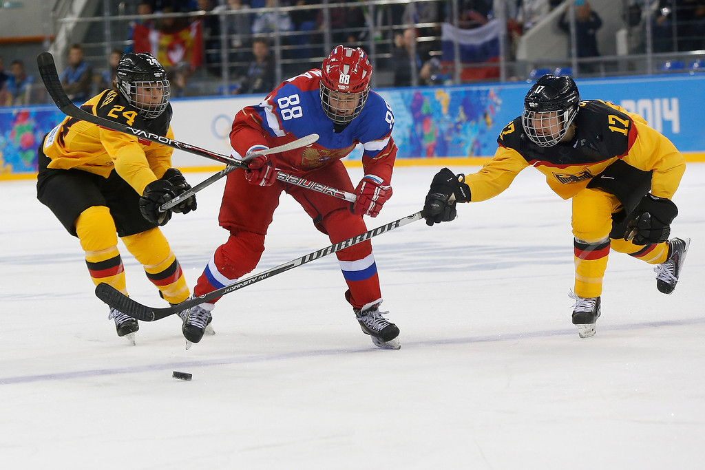 . Yekaterina Smolina of Russia is sandwiched between Lisa Christine Schuster, left and Sara Seiler of Germany as they battle for the puck during the first period of the 2014 Winter Olympics women\'s ice hockey game at Shayba Arena, Sunday, Feb. 9, 2014, in Sochi, Russia. (AP Photo/Petr David Josek)