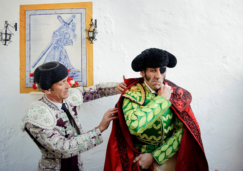 . In this March 4, 2012 photo, Spanish bullfighter Juan Jose Padilla, right, adjusts his \'capote\' before a bullfight in the southwestern Spanish town of Olivenza. This photo is one in a series of images by Associated Press photographer Daniel Ochoa de Olza that won the second place prize for the Observed Portrait series category in the World Press Photo 2013 photo contest.  (AP Photo/Daniel Ochoa de Olza, File)