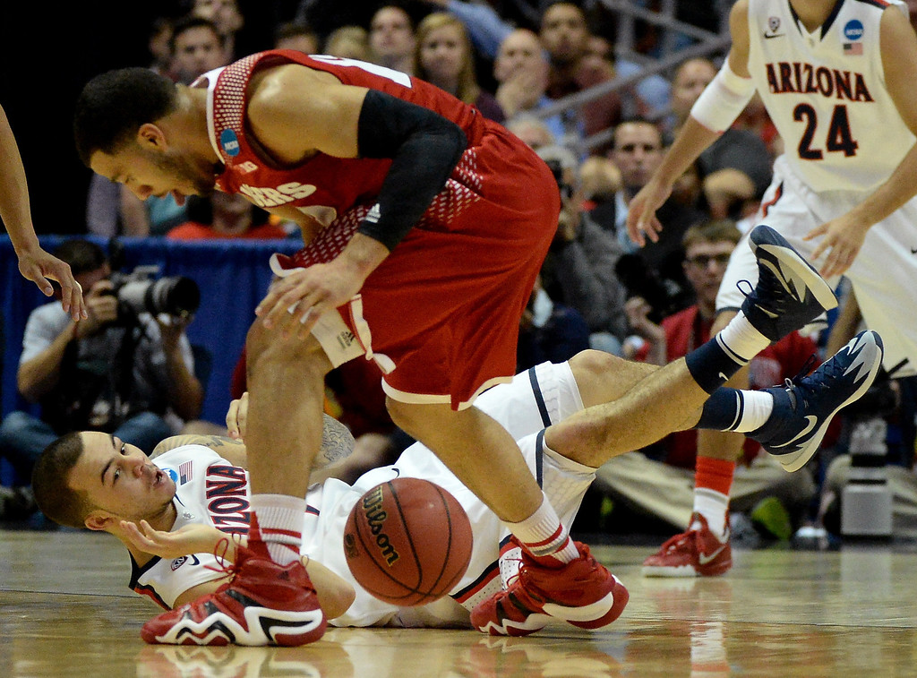 . Gabe York #1 of the Arizona Wildcats dives for a loose ball against Traevon Jackson #12 of the Wisconsin Badgers in the first half during the West Regional Final of the 2014 NCAA Men\'s Basketball Tournament at the Honda Center on March 29, 2014 in Anaheim, California.  (Photo by Harry How/Getty Images)