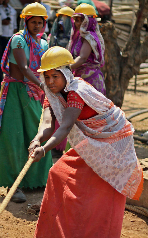 . Indian woman laborers work to lay a cable for an electricity company on International Women\'s Day in Ahmadabad, India, Friday, March 8, 2013. (AP Photo/Ajit Solanki)