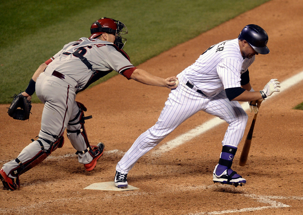 . DENVER, CO - APRIL 5:  Arizona catcher Miguel Montero (26) tagged out Colorado batter Michael Cuddyer (3) following a dropped third strike in the ninth inning. The Colorado Rockies defeated the Arizona Diamondbacks 9-4 Saturday night, April 5, 2014 in Denver. (Photo by Karl Gehring/The Denver Post)