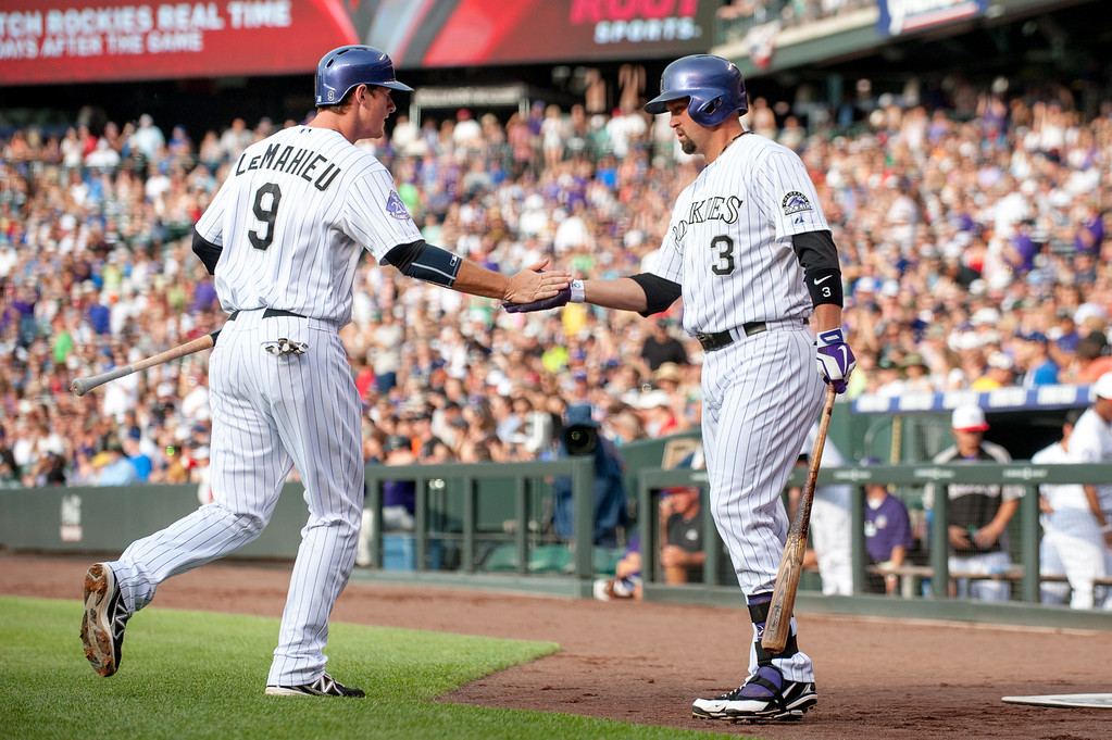 . DENVER, CO - JULY 4:  DJ LeMahieu #9 and Michael Cuddyer #3 of the Colorado Rockies celebrate a LeMahieu run off of an left fielder Carlos Gonzalez #5 (not pictured) double in the first inning of a game against the Los Angeles Dodgers at Coors Field on July 4, 2013 in Denver, Colorado. (Photo by Dustin Bradford/Getty Images)
