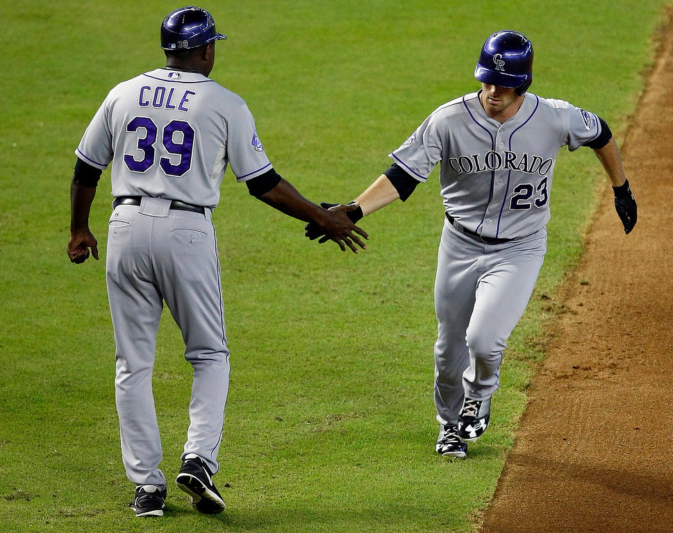 . Colorado Rockies\' Charlie Culberson (23) celebrates with third base coach Stu Cole (39) after pinch-hitting a two-run home run in the fifth inning during a baseball game against the Arizona Diamondbacks, Sunday, Sept. 15, 2013, in Phoenix. (AP Photo/Rick Scuteri)