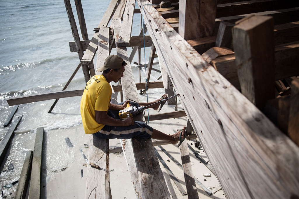 . A Buginese man drills as he tries to fix the hull of phinisi at Tanjung Bira Beach on May 2, 2014 in Bulukumba, South Sulawesi, Indonesia.  (Photo by Agung Parameswara/Getty Images)