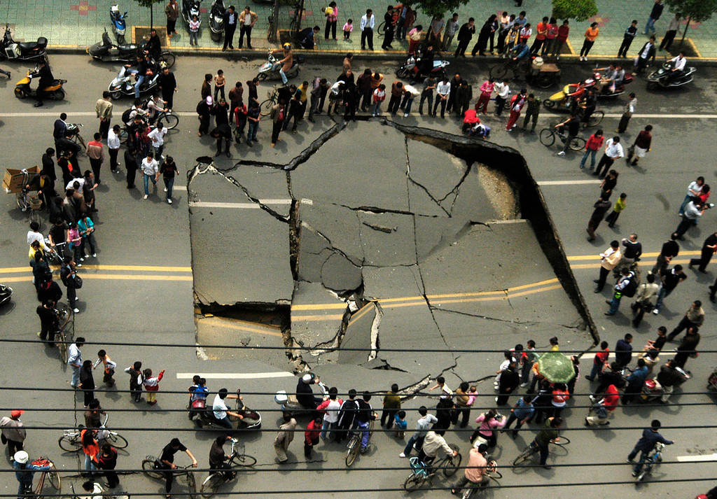 . People look at a collapsed section of Shunwai Road in Nanchang, China\'s Jiangxi province, April 25, 2007. No one was injured in the accident and further investigations are underway, according to local media. Picture taken April 25, 2007. REUTERS/China Daily