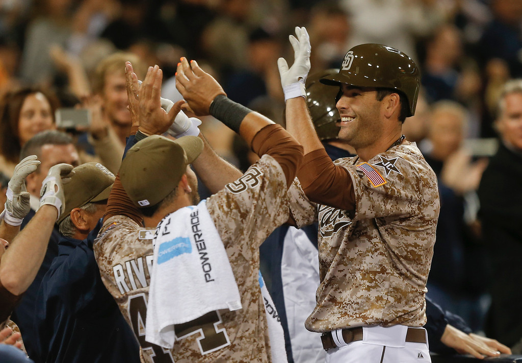 . San Diego Padres Seth Smith is greeted at the dugout after his game tieing home run against the Los Angeles Dodgers in the eighth inning of the opening game of Major League baseball in the United States Sunday, March 30, 2014, in San Diego.  (AP Photo/Lenny Ignelzi)