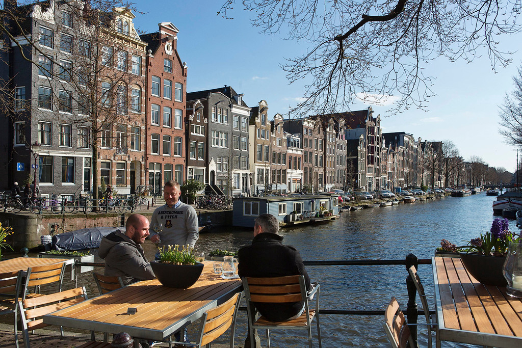 . Men enjoy the afternoon sun at the Brouwersgracht canal in Amsterdam April 2, 2013. The Royal celebrations in the Netherlands this week put the country and the capital Amsterdam on front pages and television screens around the world with an orange splash.  There\'s plenty to see and do in 48 hours in this compact city, where the world-famous Rijksmuseum only recently reopened after an extensive renovation. Picture taken April 2, 2013. REUTERS/Michael Kooren